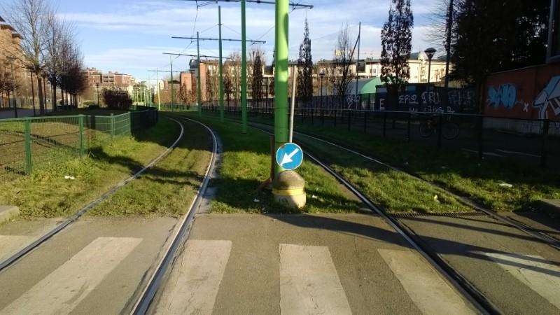 Segnale di freccia non-sense tra i binari del tram 7